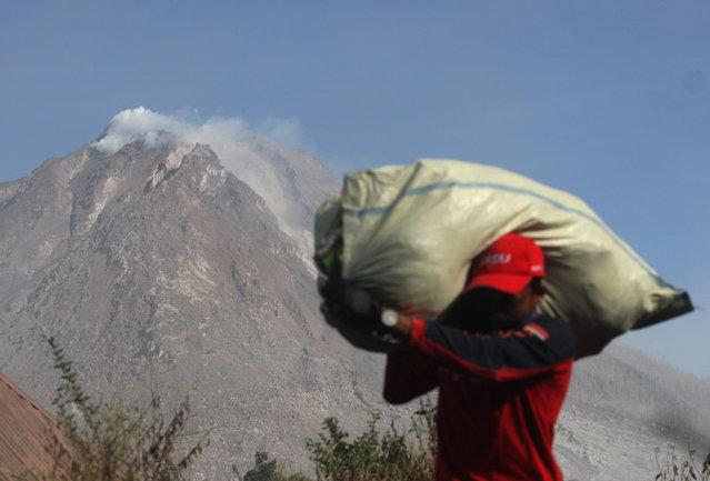 A villager carries his belonging during an evacuation following the eruption of Mount Sinabung in Gamber village, North Sumatra, Indonesia, Sunday, May 22, 2016. (Photo by Binsar Bakkara/AP Photo)