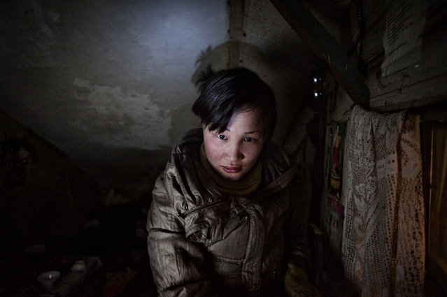 Asia, Mongolia, Ulaan Baator, March 22, 2011. Dyun Erdene, 26-year-old, former shepherd, in the tight space she shares with her family - her 55 years old father, a former shepherd, her mother, one sister and her 4-year-old nephew – in Ulaan Baator. She used to live with her family in Gobi-Ugtaal in the Dunggobi province, but during the Dzud they lost their 150 animals and, therefore, they decided to move to the city. She is pregnant but her boyfriend left her and now she is alone. (Photo by Alessandro Grassani)