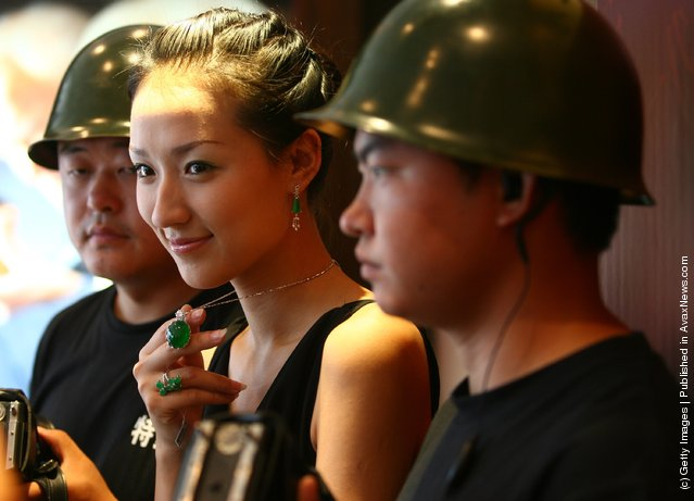 A model escorted by security guards, displays a emerald pendant worth about 28 million yuan (about USD 3.71 million), at a jewelry shop