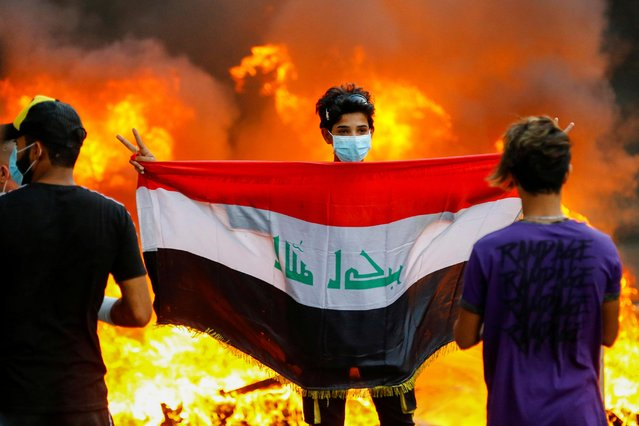 A demonstrator carries an Iraqi flag during ongoing anti-government protests in Baghdad, Iraq on November 4, 2019. (Photo by Thaier Al-Sudani/Reuters)