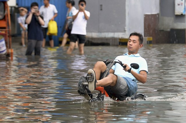 A man rides a improvised bicycle, which can travel through water, at a flooded street after heavy rainfall hit Wuhan, Hubei province, China, July 23, 2015. Severe downpours hit the city on Thursday, flooding streets and shutting down public transportations, local media reported. (Photo by Reuters/China Daily)