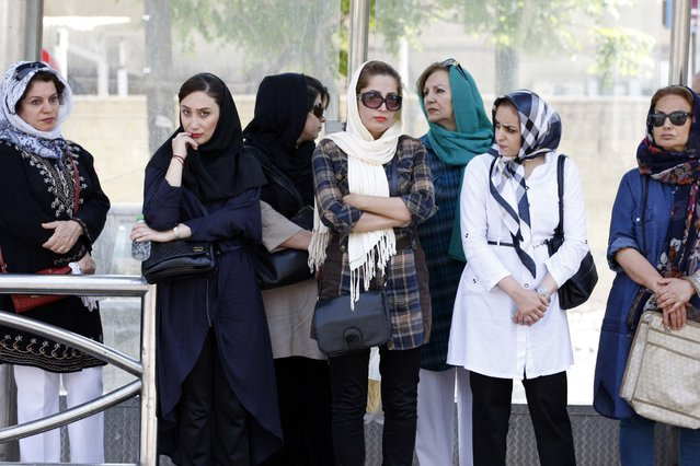 Women wait at a bus stop in northern Tehran, Iran, July 27, 2015. (Photo by Reuters/TIMA)