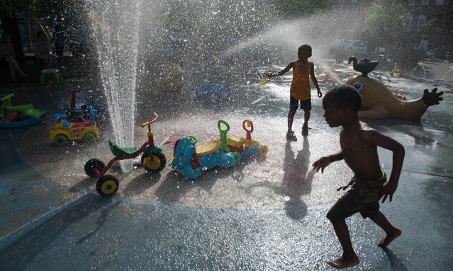 Children run through the sprinklers at a playground on May 29, 2016 in the Brooklyn borough of New York City. New York City is experiencing higher than average temperatures for the holiday weekend. (Photo by Stephanie Keith/Getty Images)