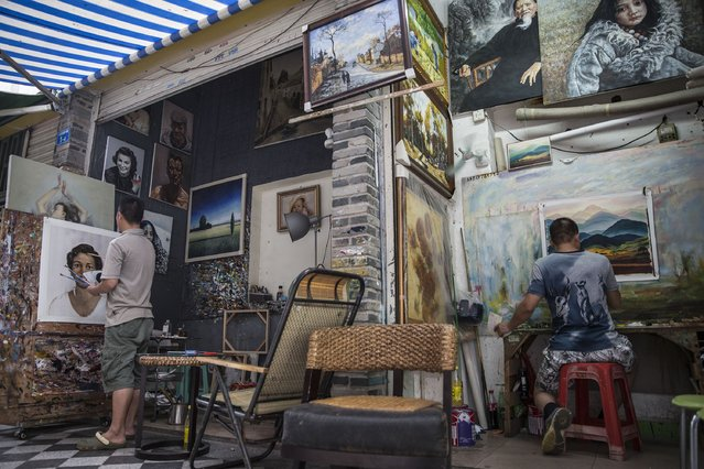Two painters work at open-sided galleries in a laneway at the artist village on June 12, 2014 in Shenzhen, China. The Dafen Artist Village in Guangdong province, China, is home to thousands of artists who reproduce some of the world's most iconic paintings as well as create their own works. The village, on the outskirts of Shenzhen, is becoming a major center for original Chinese art. (Photo by Palani Mohan/Getty images)