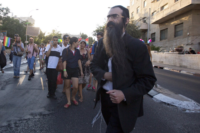 Ultra-Orthodox Jew Yishai Schlissel walks through a Gay Pride parade and is just about to pull a knife from under his coat and start stabbing people in Jerusalem, Thursday, July 30, 2015. Schlissel was recently released from prison after serving a term for stabbing several people at a gay pride parade in 2005, a police spokeswoman said. (Photo by Sebastian Scheiner/AP Photo)