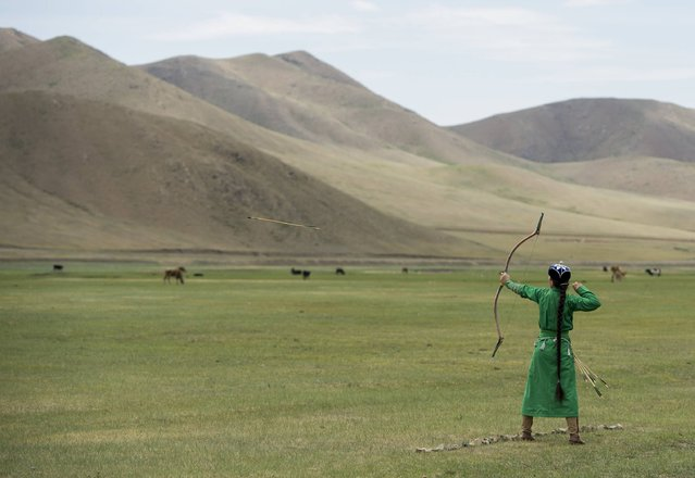 A Mongolian archer shoots a bow and arrow as US Secretary of State John Kerry attends a Naadam ceremony, a competition which traditionally includes horse racing, Mongolian wrestling and archery, in Ulan Bator, Mongolia on June 5, 2016. (Photo by Saul Loeb/AFP Photo)
