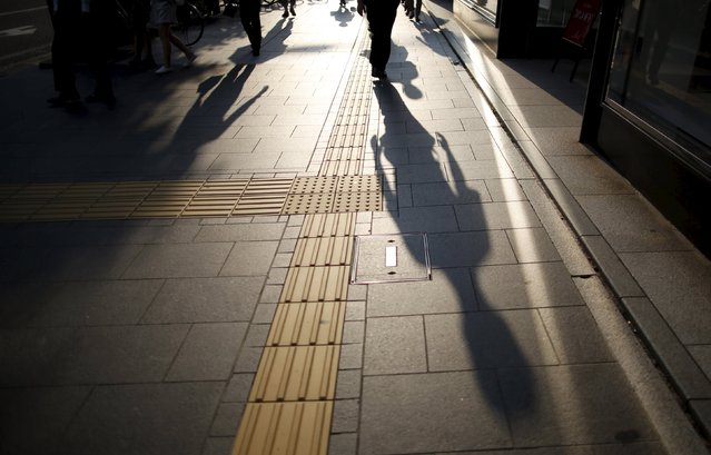 People cast long shadows on a street they are walking down, in Hiroshima, western Japan July 28, 2015. (Photo by Issei Kato/Reuters)