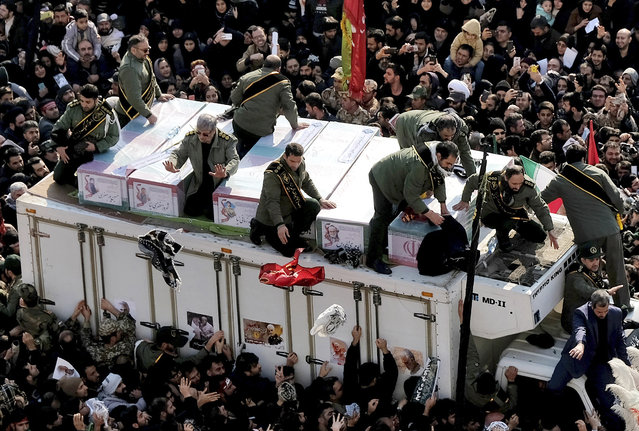 Coffins of Gen. Qassem Soleimani and others who were killed in Iraq by a U.S. drone strike, are carried on a truck surrounded by mourners during a funeral procession at the Enqelab-e-Eslami (Islamic Revolution) square in Tehran, Iran, Monday, January 6, 2020. The processions mark the first time Iran honored a single man with a multi-city ceremony. Not even Ayatollah Ruhollah Khomeini, who founded the Islamic Republic, received such a processional with his death in 1989. Soleimani on Monday will lie in state at Tehran's famed Musalla mosque as the revolutionary leader did before him. (Photo by Ebrahim Noroozi/AP Photo)