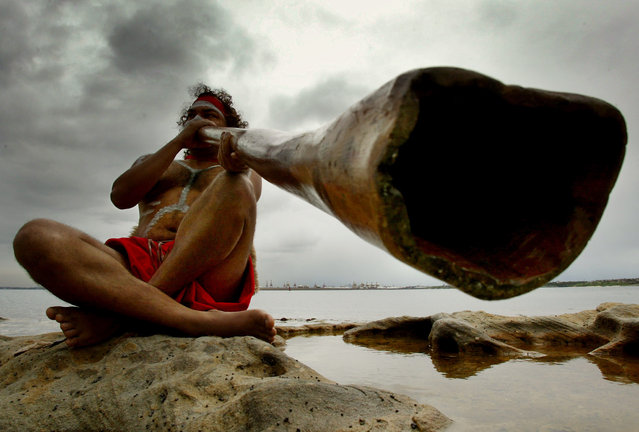 Aboriginal peformer Les Saxby plays a traditional aboriginal musical instrument known as a didgeridoo on the shores of Sydney's Botany Bay April 29, 2002. (Photo by David Gray/Reuters)