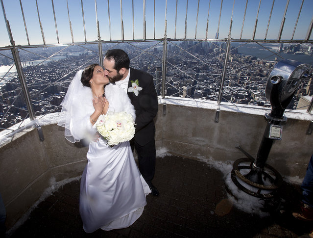 Maria Vasquez and Brendan Goldblatt kiss on the top of the Empire State Building after getting married in the Manhattan borough of New York February 14, 2014. The Empire State Building traditionally hosts weddings on St. Valentine's Day. (Photo by Carlo Allegri/Reuters)