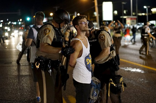 Police hold a protester who was detained in Ferguson, Missouri, August 10, 2015. (Photo by Rick Wilking/Reuters)