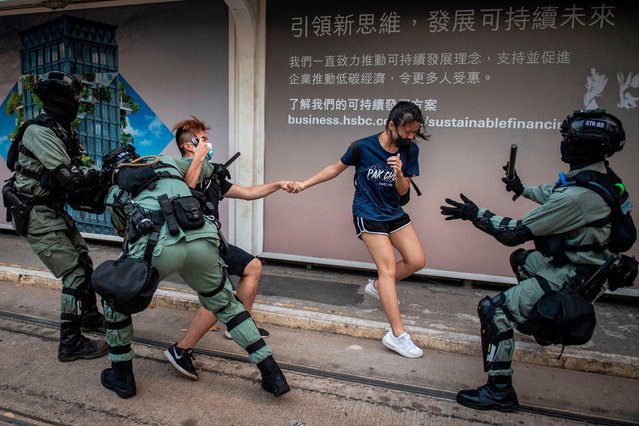 Police chase down a couple wearing facemasks in the central district in Hong Kong on October 5, 2019, a day after the city's leader outlawed face coverings at protests invoking colonial-era emergency powers not used for half a century. Masked pro-democracy protesters marched through Hong Kong in defiance of a ban on face coverings as much of the city ground to a halt on October 5, with the subway suspended and many shops shuttered following another night of violence. (Photo by Nicolas Asfouri/AFP Photo)