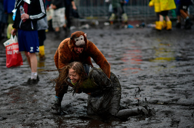 A male visitors dressed as a monkey plays with a female visitor in the mud at the muddy and flooded camping compound at the Hurricane Festival compound on June 25, 2016 in Scheessel, Germany. The Hurricane Festival was evacuated yesterday and was delayed today for the late evening, following heavy rain and thunderstorm alerts. The rain and thunderstorm have hit the festival during the night and day, causing damage to tents and flooded the festival site, only 7 concerts can be played on two stages today. The Hurricane Festival celebrates this year its 25th anniversary. 75.000 music fans have visited the Festival, but some thousands have already left the compound due to the current situation. (Photo by Alexander Koerner/Getty Images)