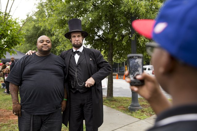 Renarldo Ellison gets his photo taken with Abraham Lincoln impersonator Dennis Boggs during a Civil War re-enactment to commemorate the 150th anniversary of the Battle of Atlanta, in Atlanta, Georgia, July 19, 2014. (Photo by Christopher Aluka Berry/Reuters)