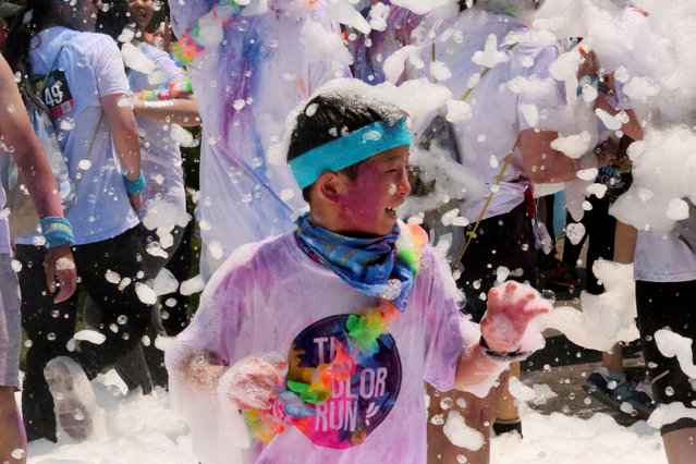A boy stands in foam during the Bejing Color Run in Beijing, June 18, 2016. (Photo by Reuters/Stringer)