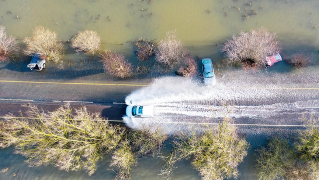 A car takes a risky journey on a partially flooded road in Welney, Norfolk, England on January 27, 2020. The other three cars had been completely submerged and four people had to be rescued from one of them. (Photo by Geoff Robinson Photography/The Times)