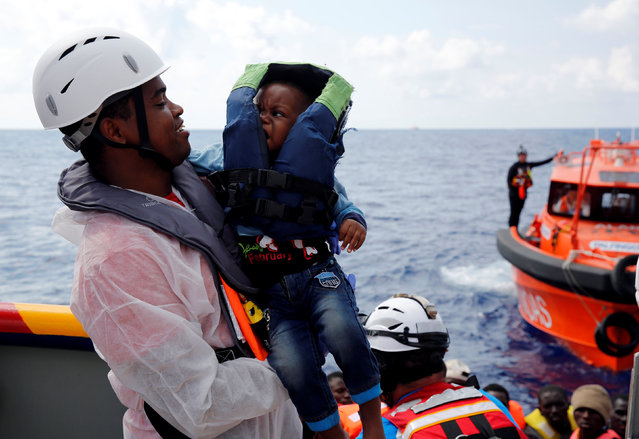 A cultural mediator from Italian NGO EMERGENCY carries a migrant baby on board the Migrant Offshore Aid Station (MOAS) rescue ship Topaz Responder around 20 nautical miles off the coast of Libya, June 23, 2016. (Photo by Darrin Zammit Lupi/Reuters)