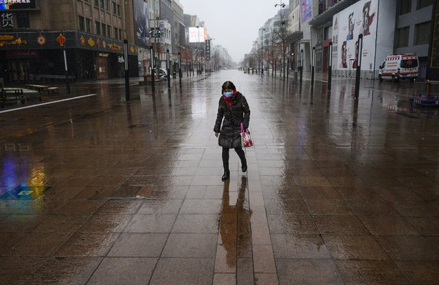 A Chinese woman wears a protective mask as she walks in a nearly empty shopping area during a light wet snowfall on February 14, 2020 in Beijing, China. The number of cases of the deadly new coronavirus COVID-19 rose to more than 55000 in mainland China Friday, in what the World Health Organization (WHO) has declared a global public health emergency. China continued to lock down the city of Wuhan in an effort to contain the spread of the pneumonia-like disease which medicals experts have confirmed can be passed from human to human. In an unprecedented move, Chinese authorities have maintained and in some cases tightened the travel restrictions on the city which is the epicentre of the virus and also in municipalities in other parts of the country affecting tens of millions of people. The number of those who have died from the virus in China climbed to over 1380 on Friday, mostly in Hubei province, and cases have been reported in other countries including the United States, Canada, Australia, Japan, South Korea, India, the United Kingdom, Germany, France and several others. The World Health Organization has warned all governments to be on alert and screening has been stepped up at airports around the world. Some countries, including the United States, have put restrictions on Chinese travellers entering and advised their citizens against travel to China. (Photo by Kevin Frayer/Getty Images)