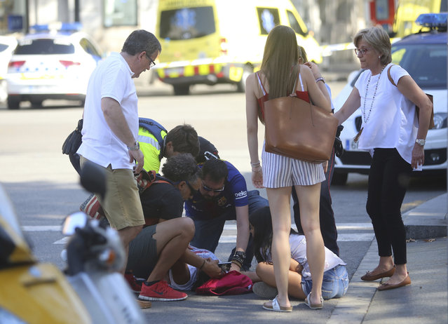 An injured person is treated in Barcelona, Spain, Thursday, August 17, 2017 after a white van jumped the sidewalk in the historic Las Ramblas district, crashing into a summer crowd of residents and tourists and injuring several people, police said. (Photo by Oriol Duran/AP Photo)