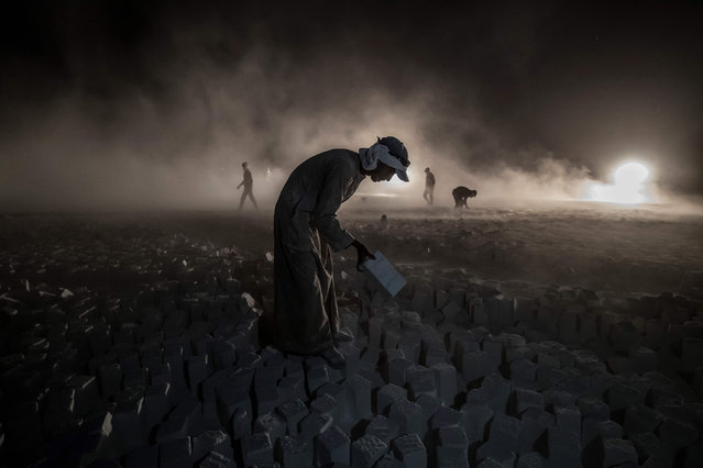 A labourer carries a stone block while working late at a limestone extraction quarry site near Egypt's southern city of Minya, some 265 kilometres south of the capital, on November 13, 2019. (Photo by Khaled Desouki/AFP Photo)