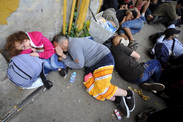 A group of immigrants who have made through police blockades rest at the Gevgelija railway station August 21, 2015. (Photo by Ognen Teofilovski/Reuters)