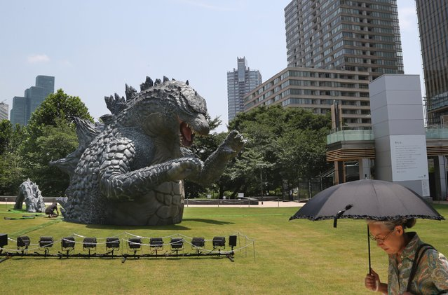 """A woman walks past a scaled down model of the new """"Godzilla"""", in Tokyo, July 17, 2014. The model is being displayed to mark Hollywood's """"Godzilla"""" remake and the 60th anniversary of the first """"Godzilla"""" movie. (Photo by Koji Sasahara/AP Photo)"""