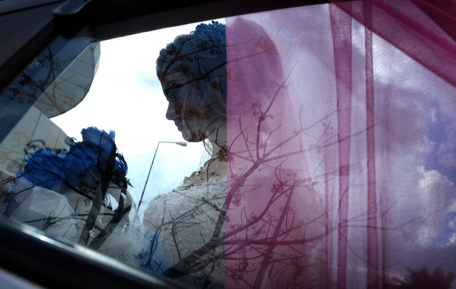 Sundus Garis, a 16-year-old displaced Iraqi woman from the Yazidi community who fled Sinjar, is pictured through a car's window during her wedding ceremony in the northernwestern Iraqi Kurdish city of Dohuk, near the border with Turkey, on January 23, 2020. Sinjar, a region west of the northern Iraqi city of Mosul that was overrun by the fanatic Islamic State (IS) group five years ago, is the historic home of the Yazidi minority which under went a brutal campaign waged by IS jihadists who forced children to become soldiers and used thousands of women as s*x slaves. Only a sliver of Sinjar's native population of 500,000 Yazidis has returned since their region was taken back by Iraqi forces from IS in 2017, with the rest saying persistent destruction, the lack of services and the tense security situation have kept them in camps. (Photo by Safin Hamed/AFP Photo)