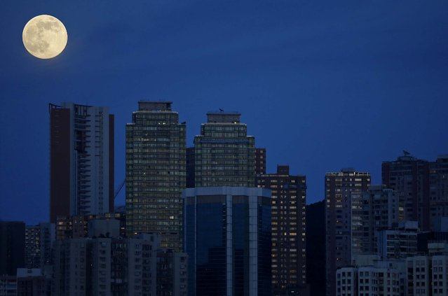 A perigee moon, also known as a Supermoon, rises over high rise buildings in Hong Kong , August 10, 2014. (Photo by Vincent YuAssociated Press)