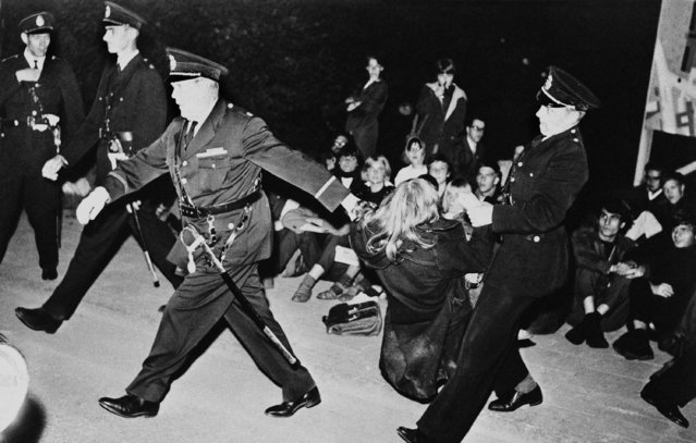 Swedish police had their hands full trying to move demonstrators into police cars and away from the U.S. embassy in Stockholm, Sweden on August 26, 1962. A girl is pulled toward the police car. Demonstrations were held outside the U.S. embassy and t he Russian embassy, in protest against nuclear testing. (Photo by AP Photo)