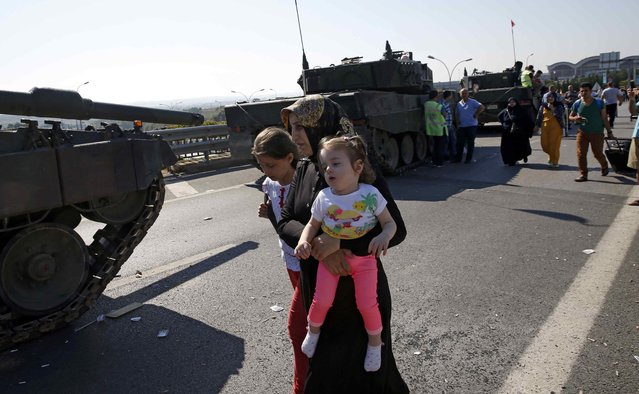A woman with two girls walks past military vehicles in front of Sabiha Airport, in Istanbul, Turkey July 16, 2016. (Photo by Baz Ratner/Reuters)