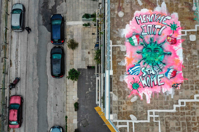 Sixteen-year-old youth artist SF paints a mural about the Covid-19 crisis on a roof in Athens, Greece on March 23, 2020. (Photo by Aris Messinis/AFP Photo)