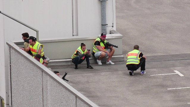 A screen grab taken from video footage shows plain clothes police officers taking cover in the car park of the Olympia shopping mall during shooting rampage in Munich, Germany July 22, 2016. (Photo by Marc Mueller/Reuters)