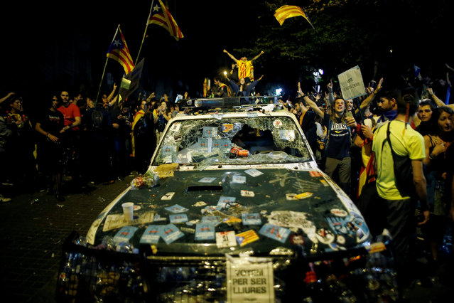 Protesters shout slogans next to a damaged Spanish Civil Guard patrol car outside the Catalan region's economy ministry building during a raid by Spanish police on government offices, in Barcelona, Spain, early September 21, 2017. (Photo by Jon Nazca/Reuters)