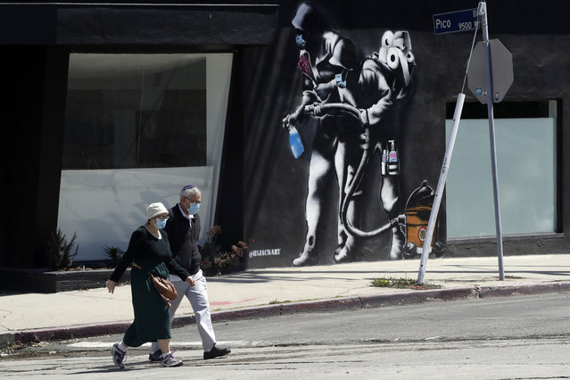 People wearing masks walk past a mural depicting a coronavirus theme during the COVID-19 pandemic Tuesday, April 14, 2020, in Los Angeles. California Gov. Gavin Newsom on Tuesday unveiled an outline for what it will take to lift coronavirus restrictions in the nation's most populous state, asking more questions than answering them as he seeks to temper the expectations of a restless, isolating public. (Photo by Marcio Jose Sanchez/AP Photo)