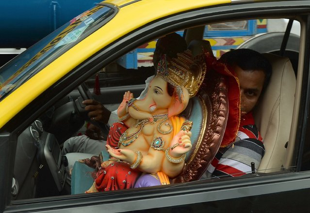 Hindu devotees transport an idol of the elephant-headed Hindu god Lord Ganesha for Ganesh Chaturthi in a taxi cab in Mumbai on August 29, 2014. The Ganesh Chaturthi festival, a popular 10-day religious festival which is annually celebrated across India, runs this year from August 29 to September 8 and culminates with the immersion of the idols in the Arabian Sea and local water bodies. (Photo by Punit Paranjpe/AFP Photo)