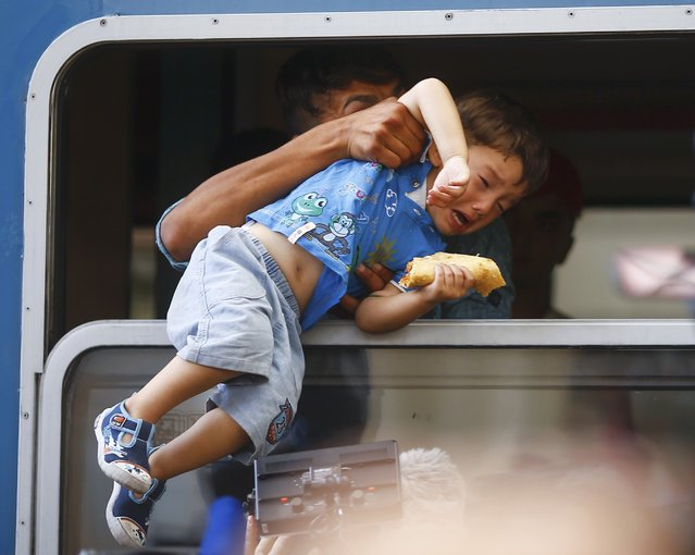 A migrant pulls a boy inside a train through a window at the Keleti train station in Budapest, Hungary, September 3, 2015. (Photo by Leonhard Foeger/Reuters)