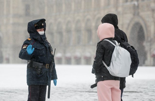 A police officer gives instructions to pedestrians, after the city authorities announced a partial lockdown ordering residents to stay at home to prevent the spread of coronavirus disease (COVID-19), during snowfall in Red Square in central Moscow, Russia on March 31, 2020. (Photo by Maxim Shemetov/Reuters)