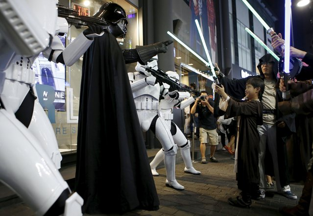 """A boy dressed as a Jedi Knight (R) from """"Star Wars"""" plays with workers dressed as Darth Vader (in black) and Storm Troopers at Myeongdong shopping district in Seoul, South Korea, September 4, 2015. (Photo by Kim Hong-Ji/Reuters)"""