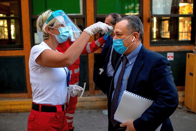 A Hellenic Red Cross volunteer wearing personal protective equipment checks the temperature of people entering the premises of a court in Athens on April 30, 2020, amid the COVID-19 outbreak caused by the novel coronavirus. The Greek prime minister announced on April 28 a gradual easing of coronavirus lockdown rules from May 4 but said implementation would be monitored daily. (Photo by Angelos Tzortzinis/AFP Photo)
