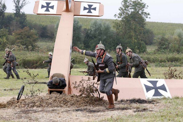 """British history enthusiast portraying German """"Feldwebelleutnant"""" officer Fritz Brandt (front) leads members of the Sturmabteilungbrandt group during the re-enactment of the First Battle of the Marne, which took place a century ago, at Chauconin-Neufmontiers, Eastern Paris September 6, 2014. (Photo by Charles Platiau/Reuters)"""