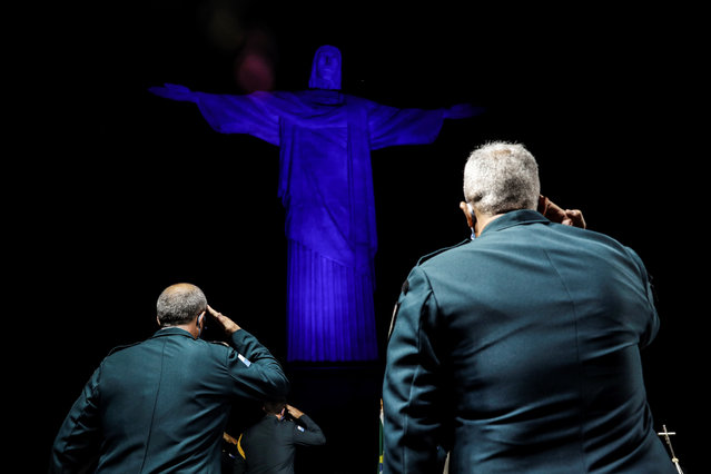 Officials of the Military Police of Rio de Janeiro participate in an act of celebration for the 211 years of the police, at the monument of Christ the Redeemer, illuminated in blue in tribute to them, in Rio de Janeiro, Brazil, 13 May 2020. (Photo by Antonio Lacerda/EPA/EFE)