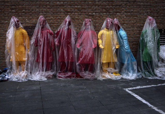 Colourful statues replicating China's famous Terracotta Warriors are covered in plastic before being placed at an exhibtion on September 3, 2014 in Beijing, China.  (Photo by Kevin Frayer/Getty Images)