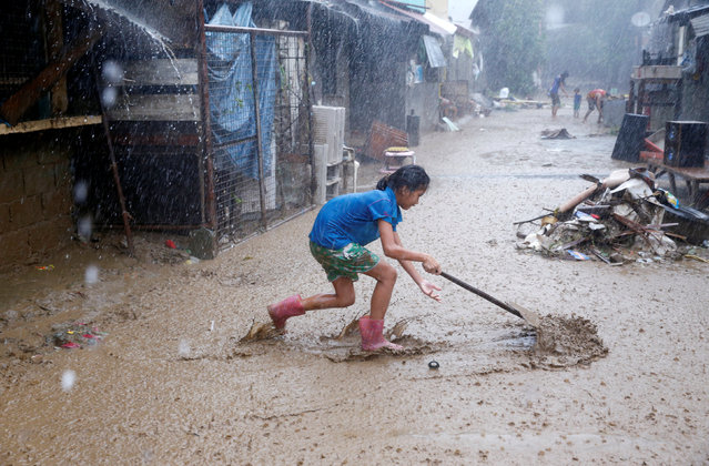A resident removes mud on a street brought by monsoon rains in San Mateo, Rizal, Philippines, August 14, 2016. (Photo by Erik De Castro/Reuters)