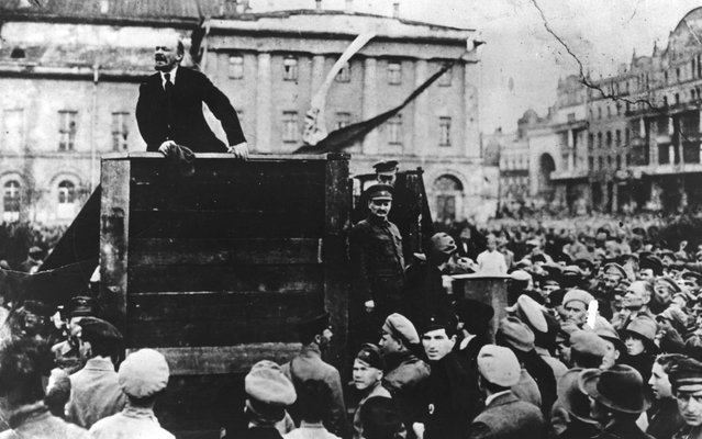 Russian revolutionary leader Vladimir Lenin (1870 - 1924) speaks to a crowd; fellow revolutionary Leon Trotsky (1879 - 1940) can be seen standing beside the platform on the right looking out over the crowd, Sverdlov Square, Moscow, May 5, 1920. (Photo by Time Life Pictures/Mansell/The LIFE Picture Collection/Getty Images)