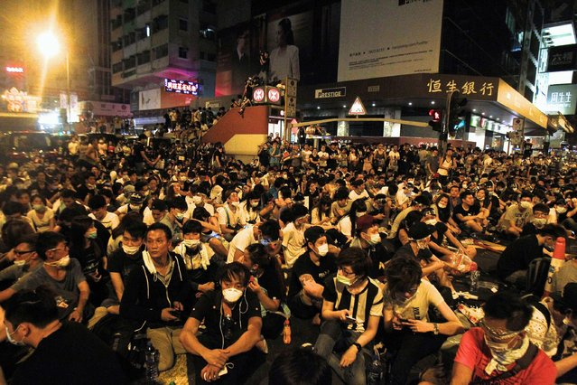Hundreds of protesters block a main road at Hong Kong's shopping Mongkok district September 29, 2014. Riot police advanced on Hong Kong democracy protesters in the early hours of Monday, firing volleys of tear gas after launching a baton-charge in the worst unrest there since China took back control of the former British colony two decades ago. (Photo by Liau Chung-ren/Reuters)