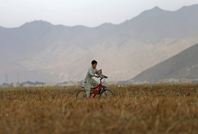 An Afghan boy rides a bicycle through a dry lake in Kabul, Afghanistan August 16, 2015. (Photo by Mohammad Ismail/Reuters)