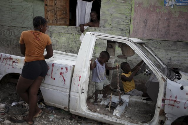 A woman talks to a man as two children play inside a wrecked car at a camp for displaced people in Port-au-Prince, Haiti, March 6, 2016. (Photo by Andres Martinez Casares/Reuters)