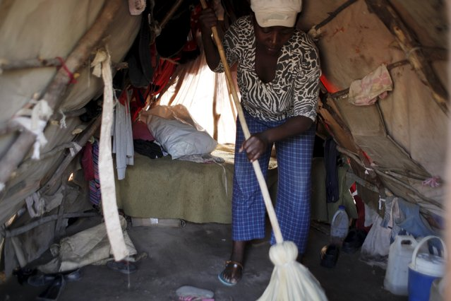 Gasly Laduceur sweeps the dirt floor with a broom inside a makeshift tent at a refugee camp for Haitians returning from the Dominican Republic on the outskirts of Anse-a-Pitres, Haiti, September 7, 2015. (Photo by Andres Martinez Casares/Reuters)