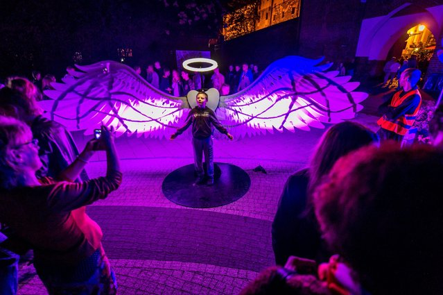 """The light installation """"Angels of Freedom"""" by Israeli OGE Creative Group is displayed at a street during the Bella Skyway Festival 2016 in Torun, Poland, 23 August 2016. The Festival has been organised in Torun since 2009. The programme of this event is based on three pillars: science, art and people. Festival presents light-art installations and shows performed by artists from around the world. (Photo by Tytus Zmijewski/EPA)"""