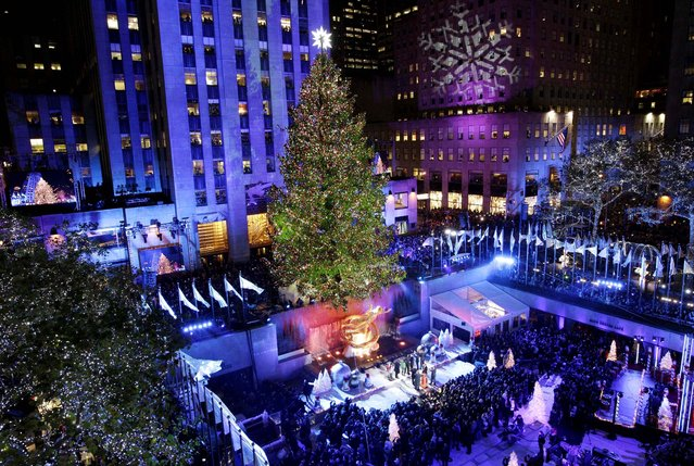 The Rockefeller Center Christmas tree is lit during the 80th annual tree lighting ceremony at Rockefeller Center in New York. (Photo by Kathy Willens/Associated Press)